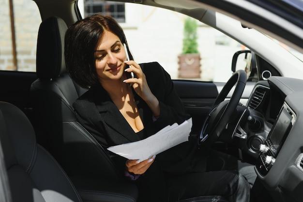 Businesswoman sitting in siège du conducteur dans sa voiture à l'aide du téléphone