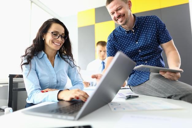Businesswoman sourit et travaille à l'ordinateur portable à côté de ses collègues