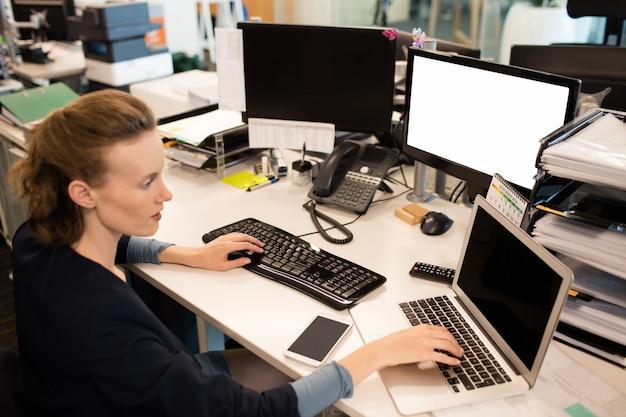 Businesswoman tapant sur ordinateur portable tout en utilisant un ordinateur de bureau
