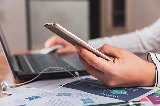 Businesswoman travaille au bureau et envoie des messages texte avec son téléphone portable