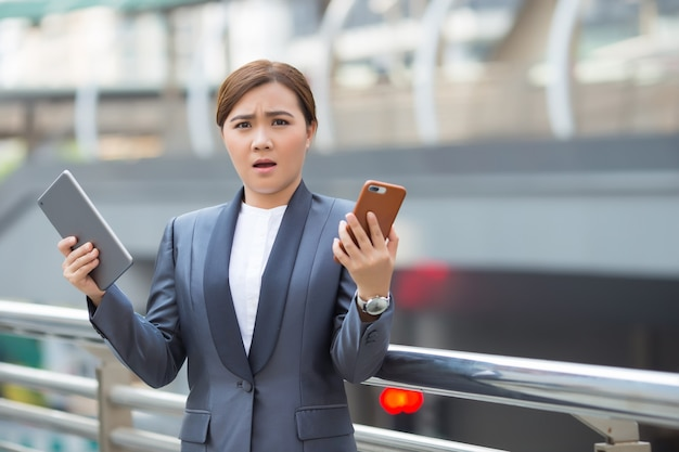 Businesswoman use tablette et smartphone a surprise