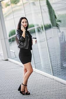 Businesswoman using digital smartphone et boire du café près de l'immeuble de bureaux.