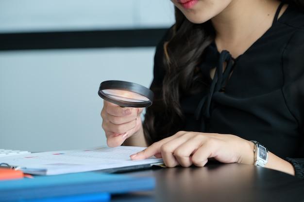 Businesswoman using loupe pour examiner le bilan annuel