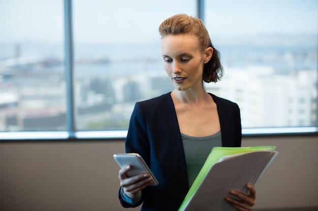 Businesswoman using mobile phone tout en maintenant des fichiers