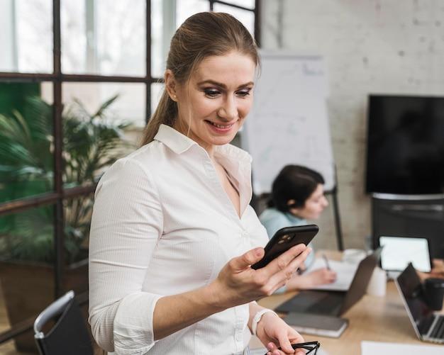 Businesswoman using smartphone lors d'une réunion