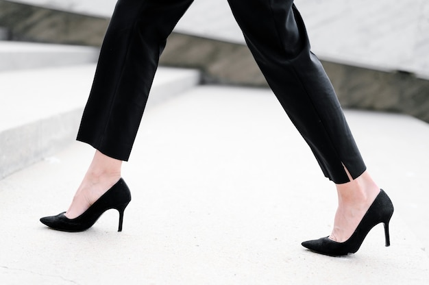 Businesswoman wearing heels monter les escaliers dans la ville