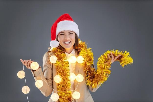 Businesswoman with santa's hat sur la tête, avec des décorations de noël autour du cou célébrant