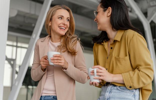 Businesswomen parlant tout en dégustant une tasse de café