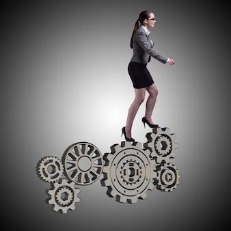 Busineswoman avec roues dentées dans le concept de travail d'équipe