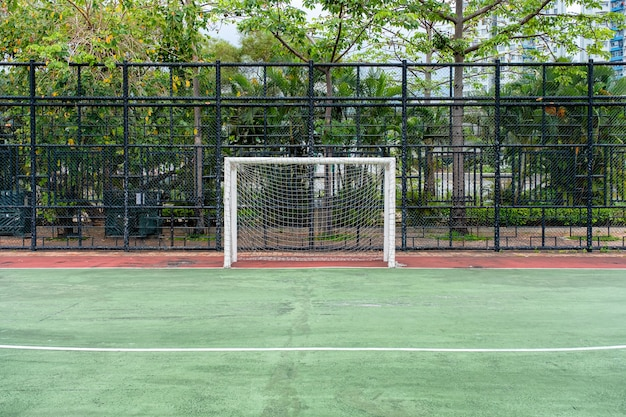 But de football avec filet dans un champ de caoutchouc vert