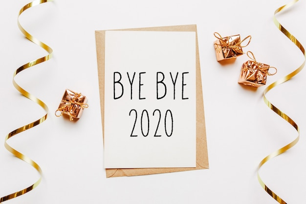 Bye bye 2020 note avec enveloppe, cadeaux et ruban d'or sur blanc