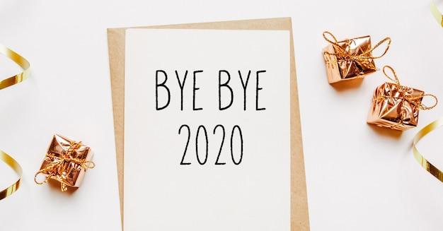 Bye bye 2020 note avec enveloppe, cadeaux et ruban d'or sur fond blanc. joyeux noël et nouvel an concept