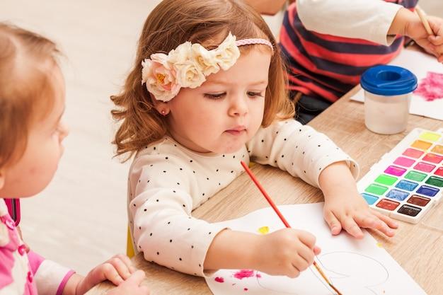 C02 ans les enfants apprennent à peindre avec un pinceau et des aquarelles sur papier à la maternelle