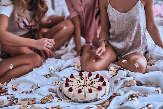 Ça a l'air délicieux. gros plan sur quatre jeunes femmes en pyjama se préparant à manger du gâteau tout en organisant une soirée pyjama