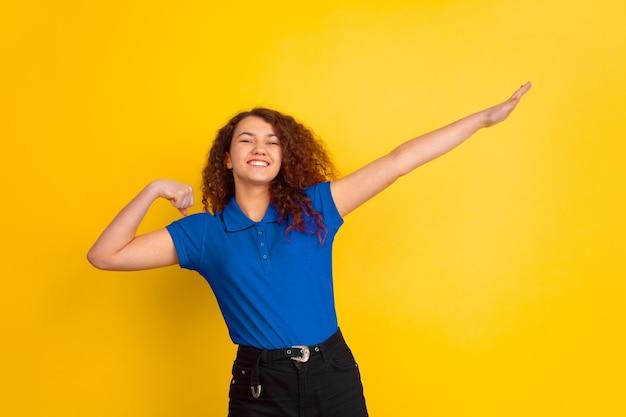 Ça a l'air mignon, geste gagnant. portrait de jeune fille de l'adolescence caucasienne sur fond de studio jaune. beau modèle féminin bouclé en chemise bleue. concept d'émotions humaines, expression faciale, ventes, publicité. copyspace.