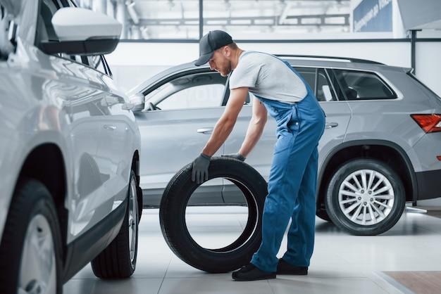 Ça a l'air parfait. mécanicien tenant un pneu au garage de réparation. remplacement des pneus d'hiver et d'été