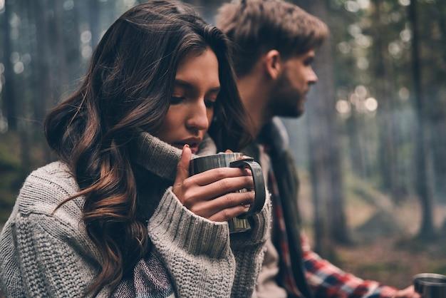 Ça sent si bon... jeune beau couple dégustant des boissons chaudes assis dans la forêt