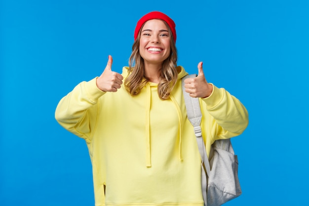 Ça sonne bien, d'accord. fille hipster joyeuse et souriante en bonnet rouge et sweat à capuche jaune, approuver l'idée, d'accord avec des amis pour choisir où sortir après les cours, tenir le sac à dos, mur bleu