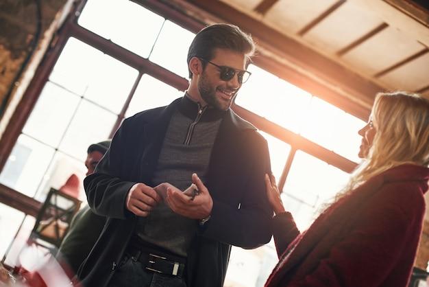 Ça vous plaît. heureux jeune couple joyeux choisissant des lunettes de soleil pour homme au petit marché de rue. jeune homme portant des lunettes de soleil et demander l'avis de sa petite amie