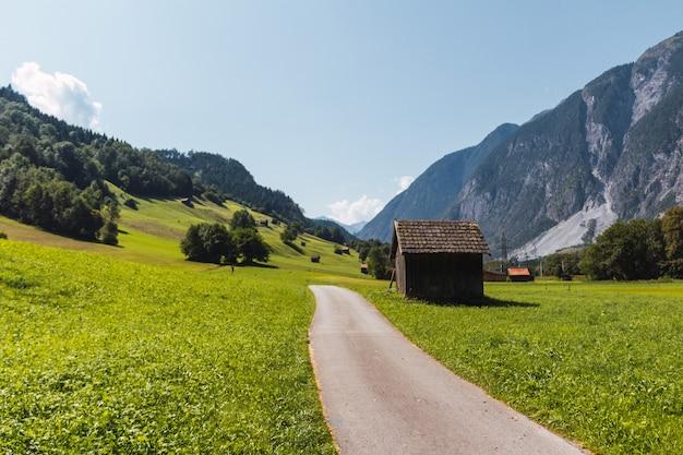 Cabane en bois rustique à côté d'une route goudronnée dans une vallée verdoyante des alpes