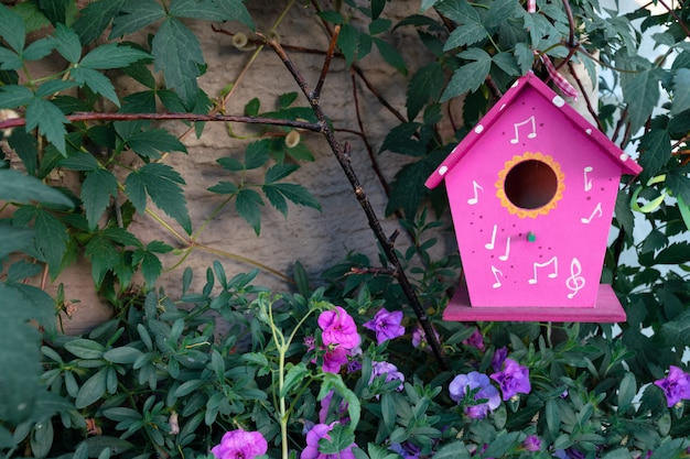 Une cabane à oiseaux rose est suspendue à un arbre entouré de fleurs de pétunia.