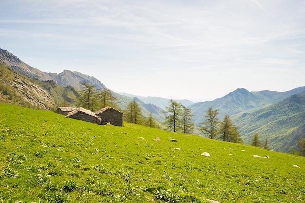 Des cabanes de pierre alpines dans un paysage vert étonnant