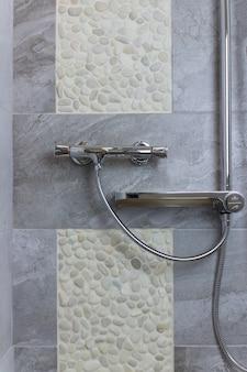 Cabine de douche d'angle avec douchette murale.