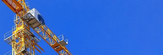 Cabine de grue de construction, photo de bannière de grue de construction jaune avec fond de ciel bleu et espace de copie
