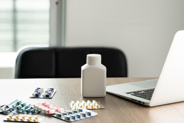 Cabinet de médecin avec ordinateur portable et médicaments