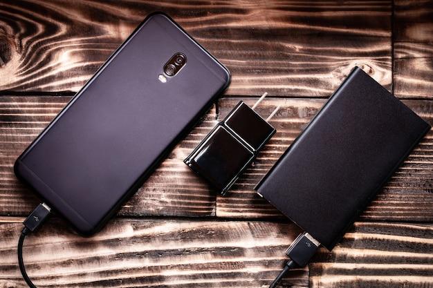 Câble de banque de téléphone intelligent et d'alimentation charge sur la texture de fond bois.