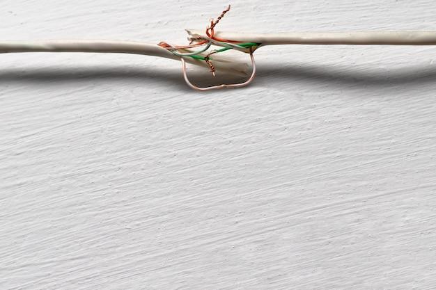 Câble cassé contre un mur blanc. les fils de cuivre sont torsadés à la main et non isolés.