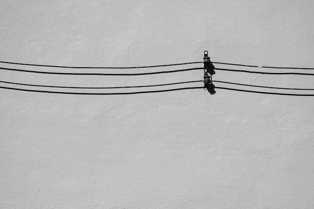 Câble noir et l'ombre sur le mur de ciment - monochrome