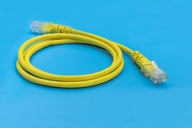 Câble réseau jaune avec connecteurs dof. sur fond bleu. fermer.