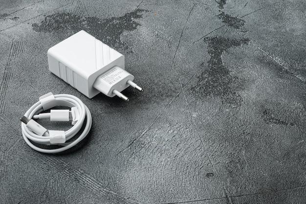 Câble usb avec jeu de prises de chargeur mural usb, sur fond de table en pierre grise, avec espace de copie pour le texte