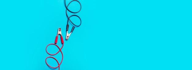 Les câbles de démarrage de la batterie sur fond bleu clair, rouge et noir sont parallèles l'un à l'autre