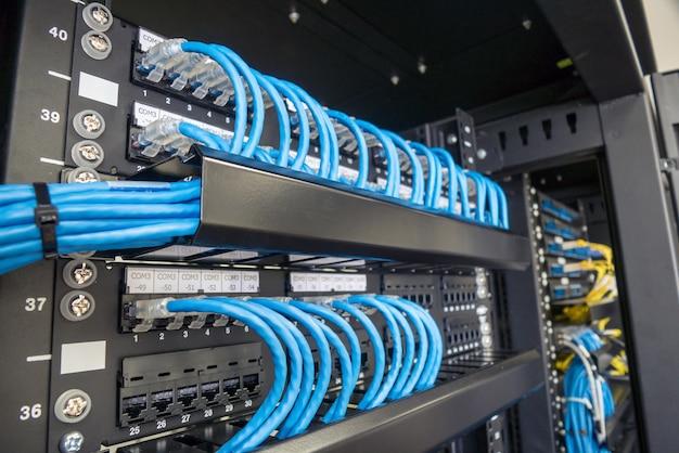Câbles ethernet et panneau de cheminement dans l'armoire rack