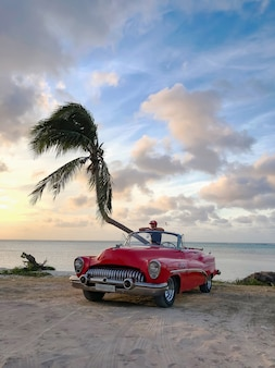 Cabriolet rouge sur une plage tropicale