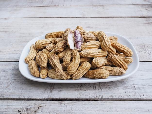Cacahuètes bouillies sur plaque sur une table en bois.