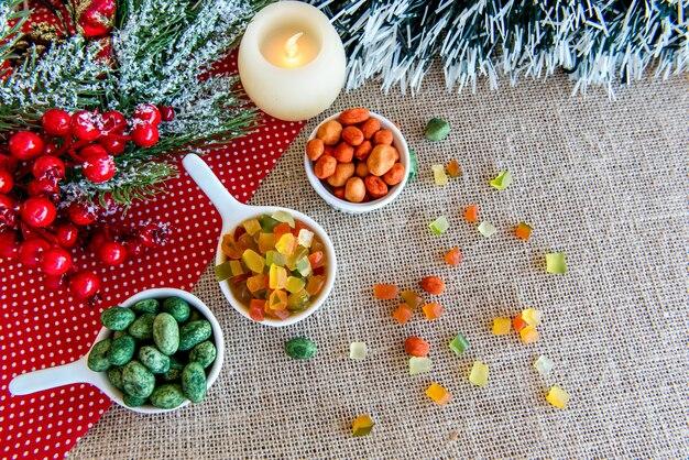 Cacahuètes colorées et fruits confits colorés sur une vue de dessus de table de noël.