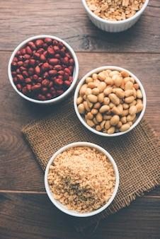 Cacahuètes concassées ou poudre de mungfali avec de l'arachide entière et grillée. servi dans un bol sur fond de mauvaise humeur. mise au point sélective