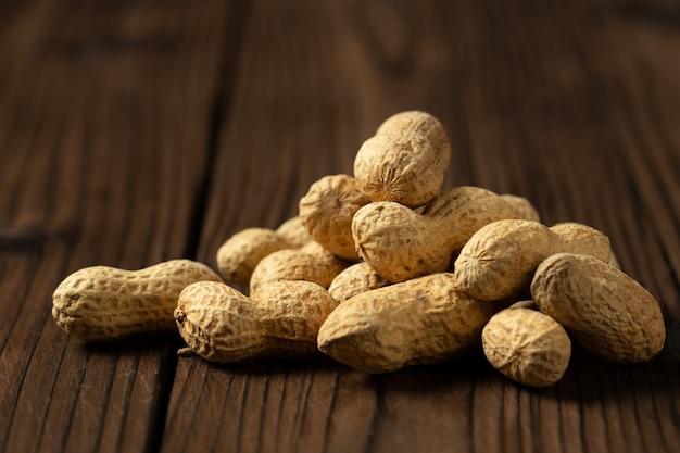 Cacahuètes en coques sur bois.