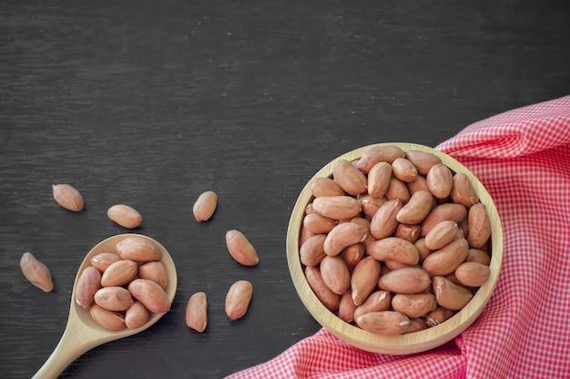 Cacahuètes crues dans un bol en bois sur fond de table