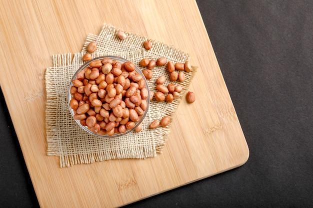 Cacahuètes dans un bol sur le fond sombre.