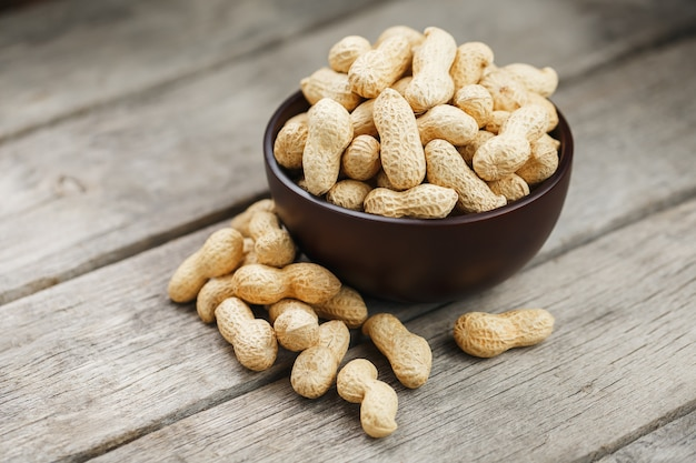 Cacahuètes dans la coquille, dans une tasse en bois sur la table.