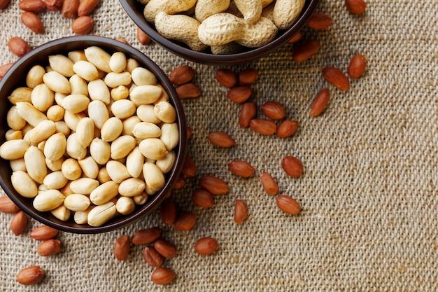 Cacahuètes dans la coquille et pelées gros plan dans une tasse
