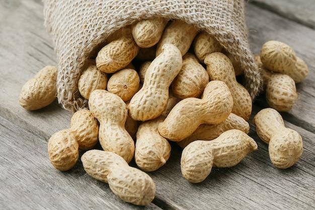 Cacahuètes dans un sac de jute miniature sur une vieille surface en bois grise
