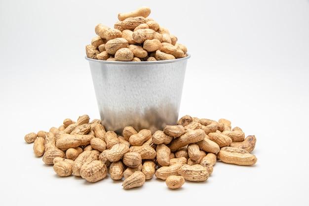 Cacahuètes dans un seau en fer blanc sur blanc