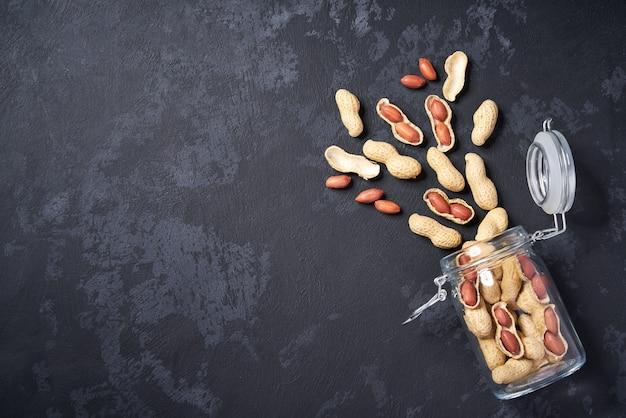 Cacahuètes décortiquées et non décortiquées dans un bocal en verre ouvert sur une table noire, avec espace pour les copies. vue de dessus.