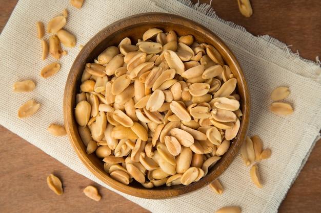 Cacahuètes grillées dans un bol en bois mettant sur lin et fond en bois.