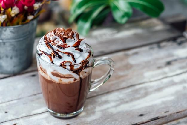 Cacao au chocolat chaud dans une tasse en verre avec crème fouettée